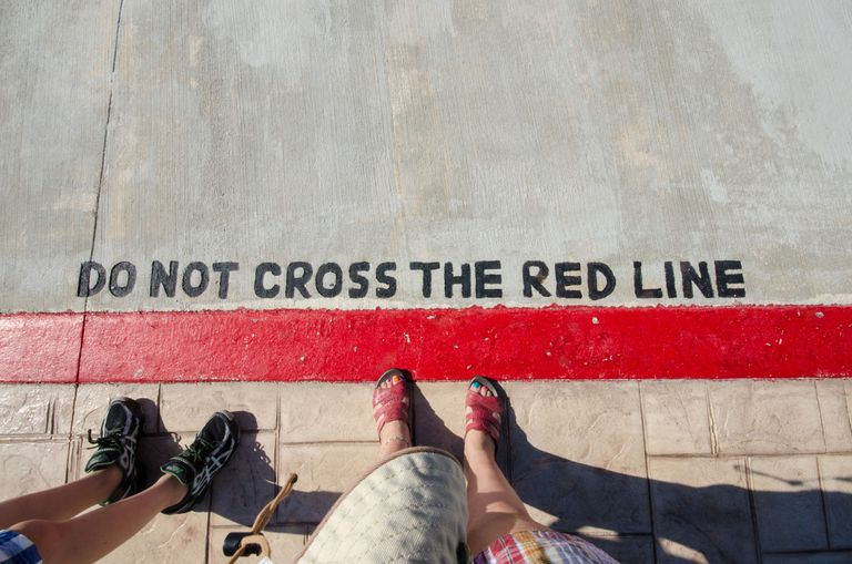 Photo of a road with Do Not Cross The Red Line written on it