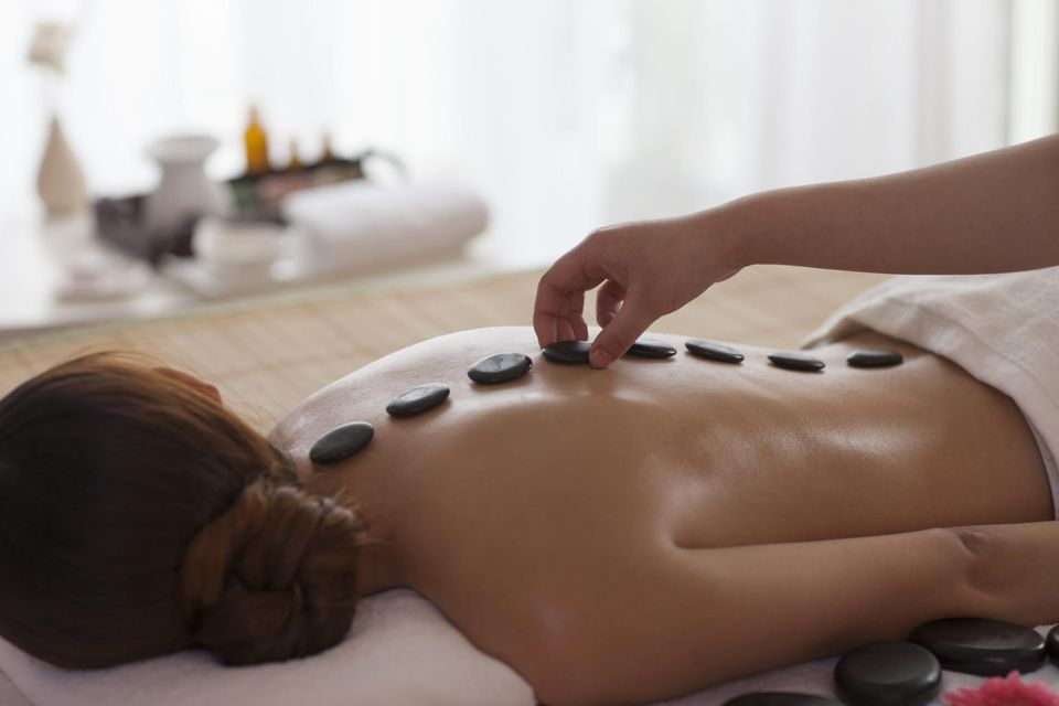 Asian woman getting stone massage in spa