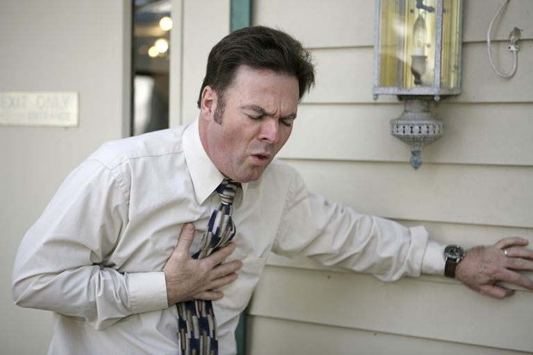man holding his chest coughing