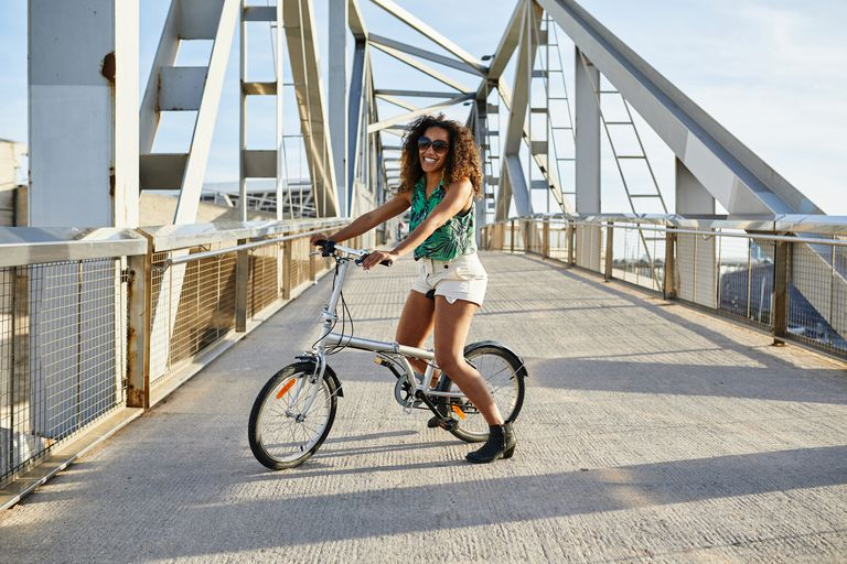 Woman riding bike on bridge path