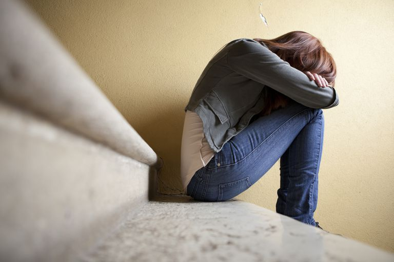 Depressed woman sitting on steps