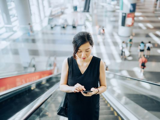 Young businesswoman reading emails on smartphone while riding on escalator
