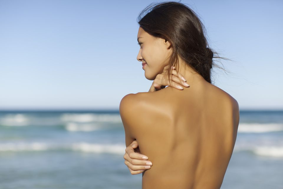 Naked young woman looking at ocean, rear view