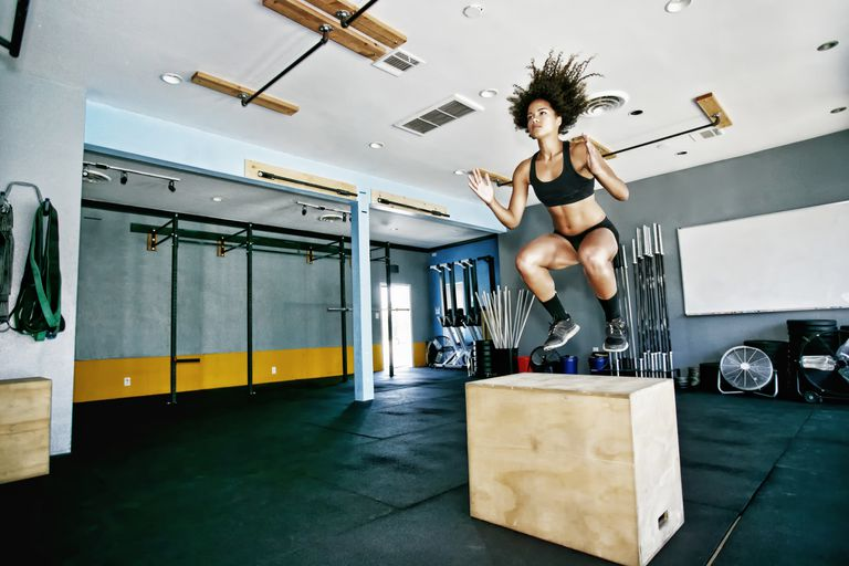 woman doing plyometric box jump exercise in gym