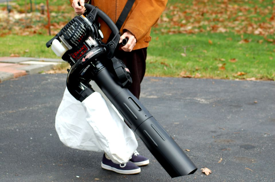 Woman holding Craftsman 4-cycle gas leaf blower vacuum.