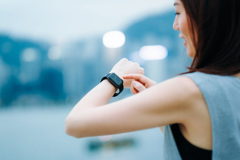 Confident businesswoman checking financial trading data with smart watch in city