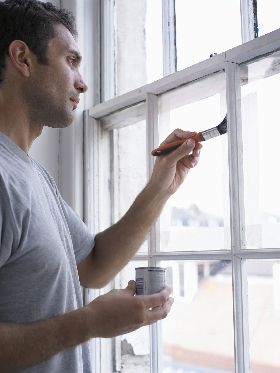 Man Holding a Paint Tin and a Paintbrush, Painting a Window Frame