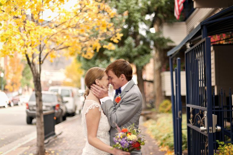 Bride and Groom Kissing On Side Walk
