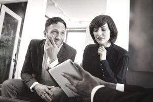 Couple in a Meeting Reading from Digital Table