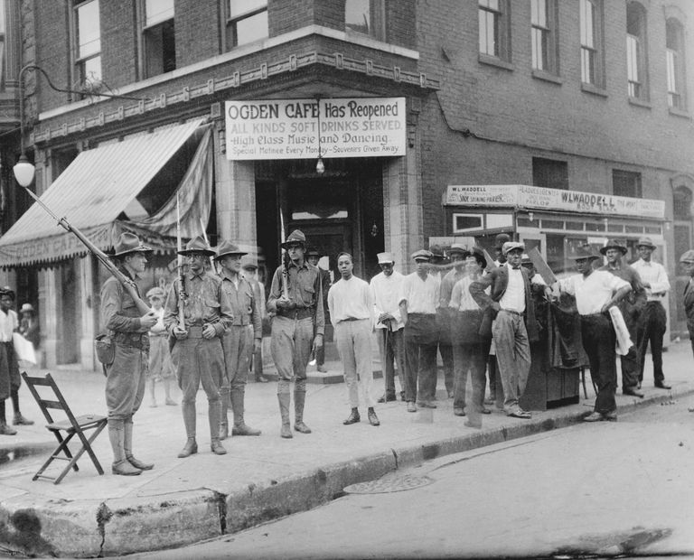 A group of African American men who have gathered in front of the Ogden Cafe, Chicago 1919.