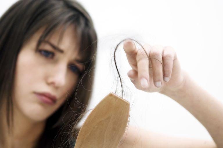 mujer preocupada con cabello caído en el cepillo