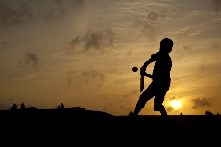 Kid playing cricket at sunset in Sri Lanka