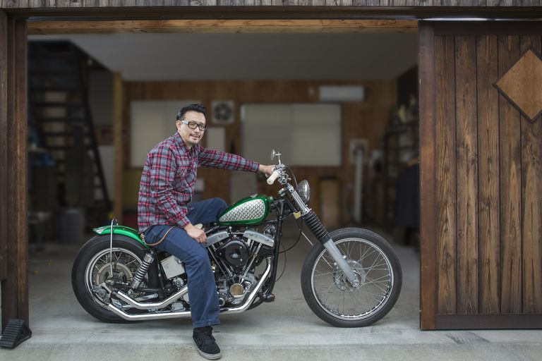 a man sitting on his motorcycle in his garage
