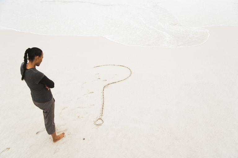 Woman looking down towards question mark drawn in sand on beach