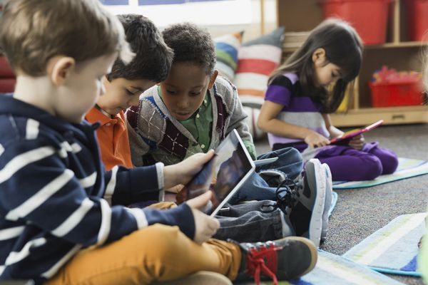 Young children play on digital tablets in school.