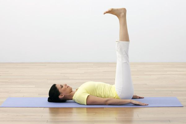 Woman performing yoga exercise, lying on her back, legs up, side view