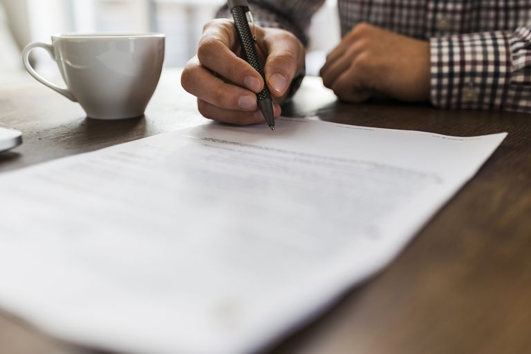 Close-up of man signing document on table