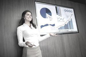 Business woman demonstrates a strong work ethic with the results she has achieved and is presenting to a group.