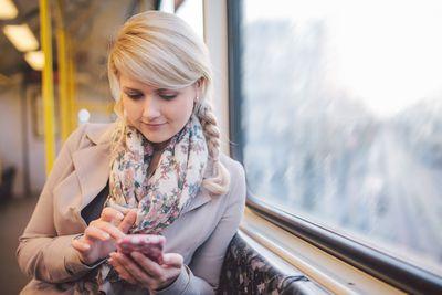 Woman using smart phone in subway