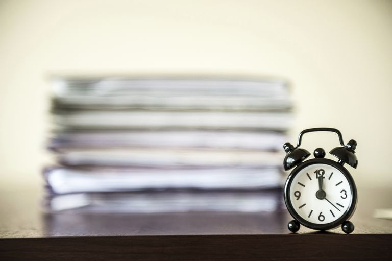 A time clock in front of a stack of paper files