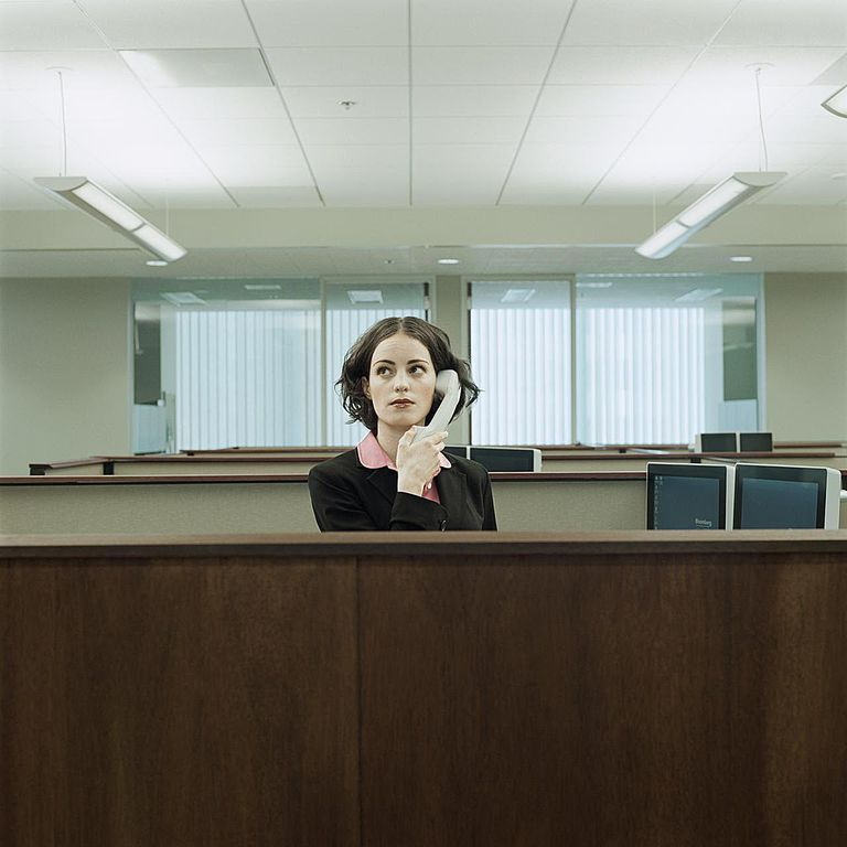 Businesswoman standing in cubicle, holding telephone