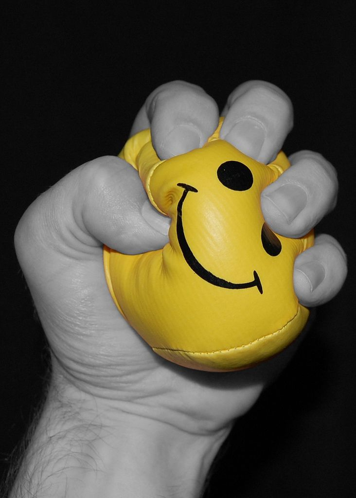 man tightly squeezing a smiley face ball