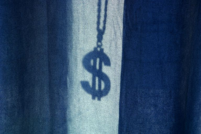 The shadow of a dollar medallion behind blue curtains.