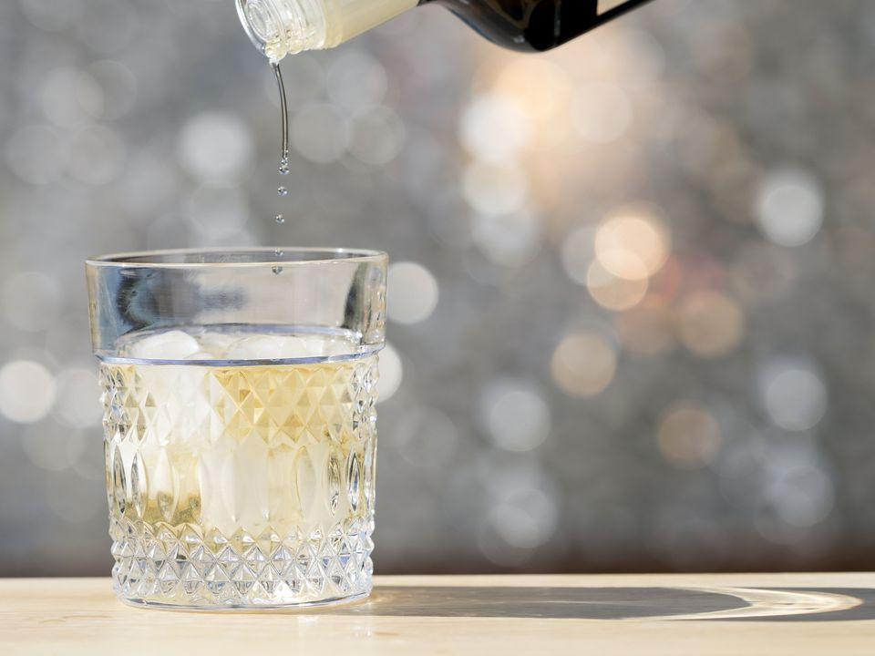 Botella de llenado de un vaso de whisky con hielo sobre una mesa al aire libre con la luz del sol