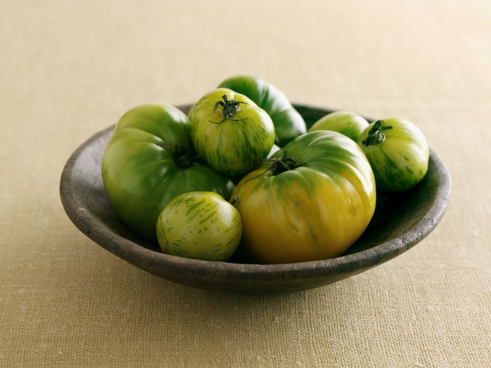 Wooden bowl containing green tomatoes