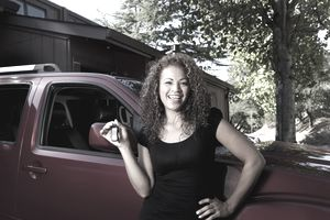 Hispanic woman holding keys to new car