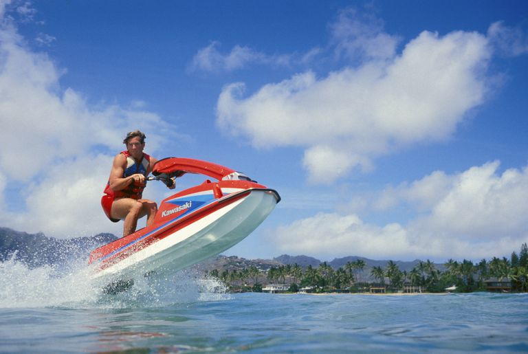 Jet skier almost airborne, looks at camera, homes and palms lined in background