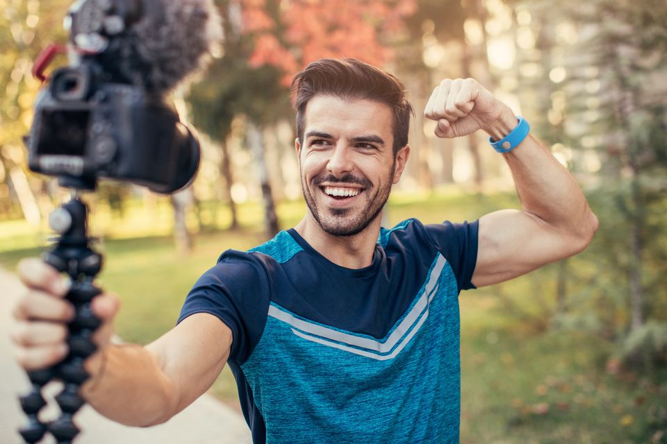 Young man flexes his muscles for a selfie