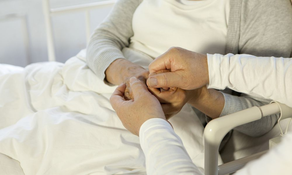 Senior man holding hands with senior woman in bed