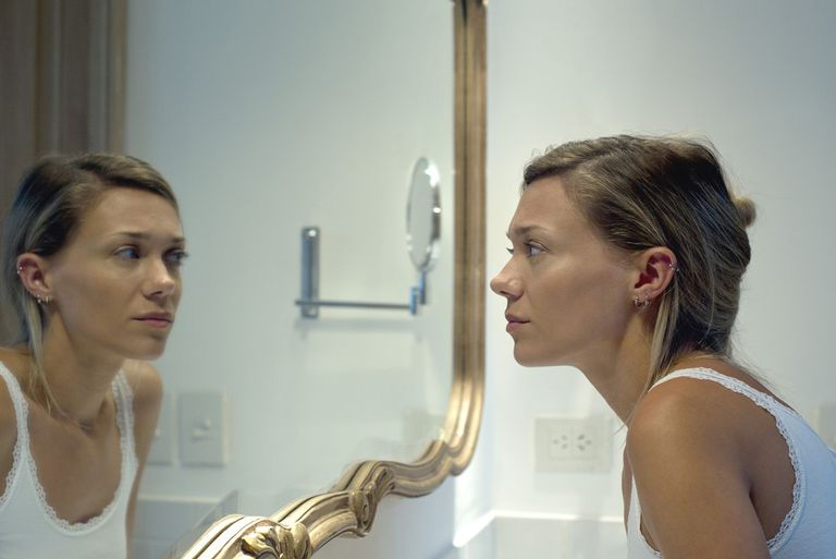 Woman looking at self in bathroom mirror