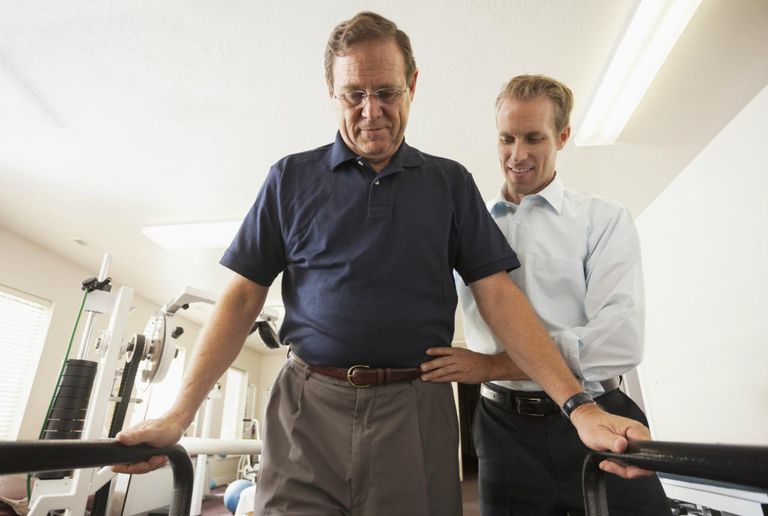 USA, Utah, Orem, Man re-learning to walk with physical therapist