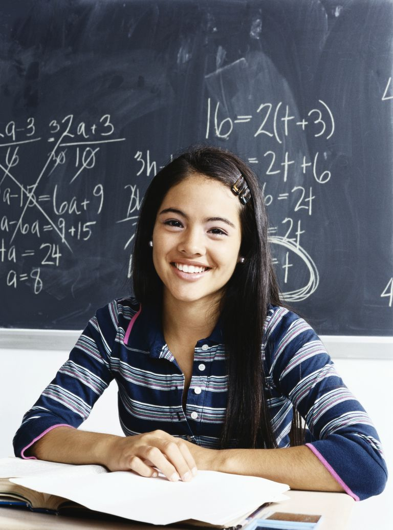 Teenage Girl Sits Smiling at a Desk in Front of a Blackboard