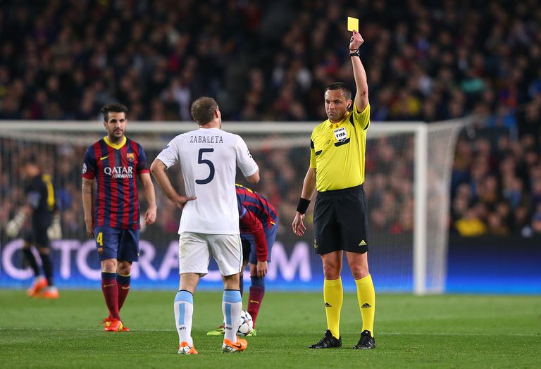 Pablo Zabaleta of Manchester City is shown the yellow card during the first half by referee Stephane Lannoy during the UEFA Champions League