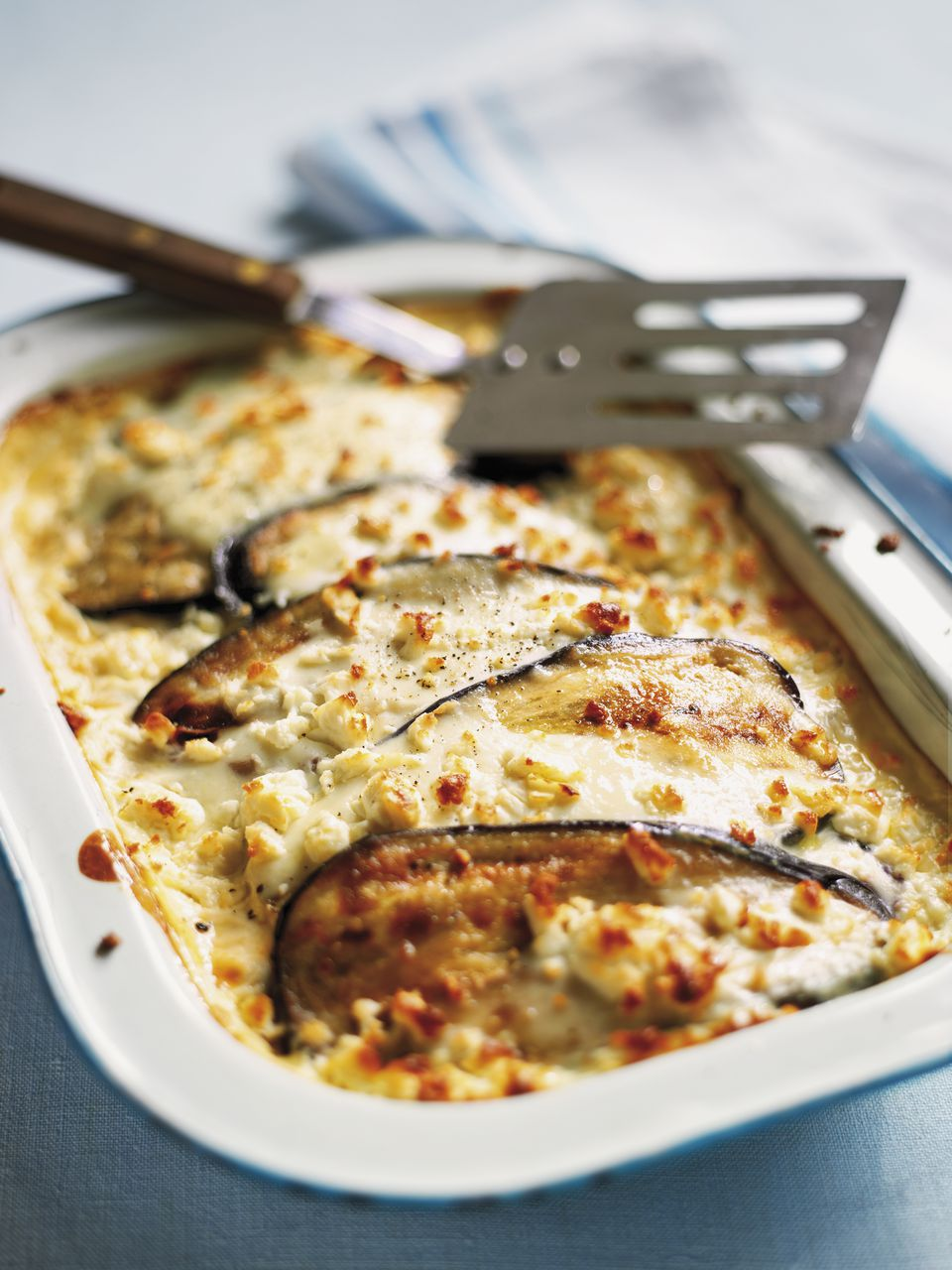 Moussaka in metal dish, with spatula, high angle view