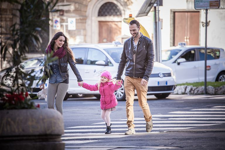 Couple and daughter holding hands on pelican crossing in Cagliari, Sardinia, Italy