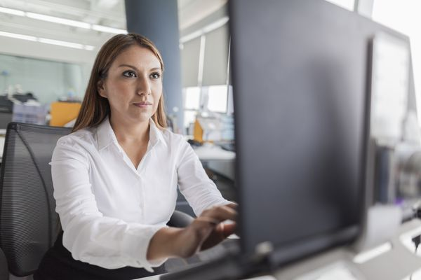 Businesswoman typing on laptop computer in office