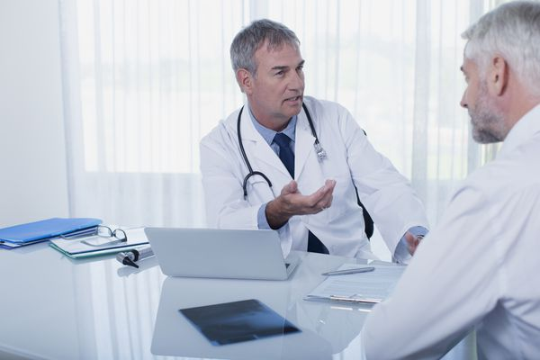 Mature doctor talking to patient at desk in office