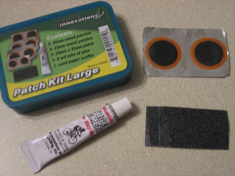 A typical bike tire patch kit with sandpaper, rubber cement and an assortment of patches.