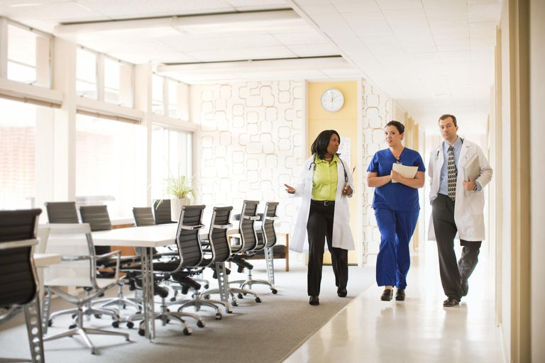 Doctors and nurse walk together down clinic or office hallway.
