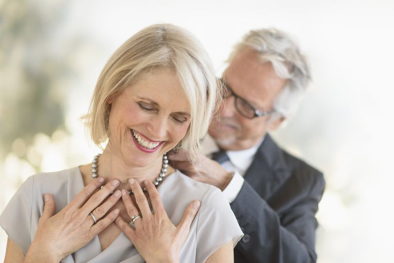 man putting necklace on woman