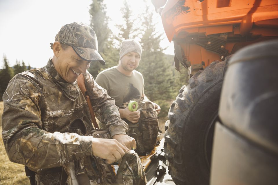 Father and son hunters preparing hunting equipment at quadbike