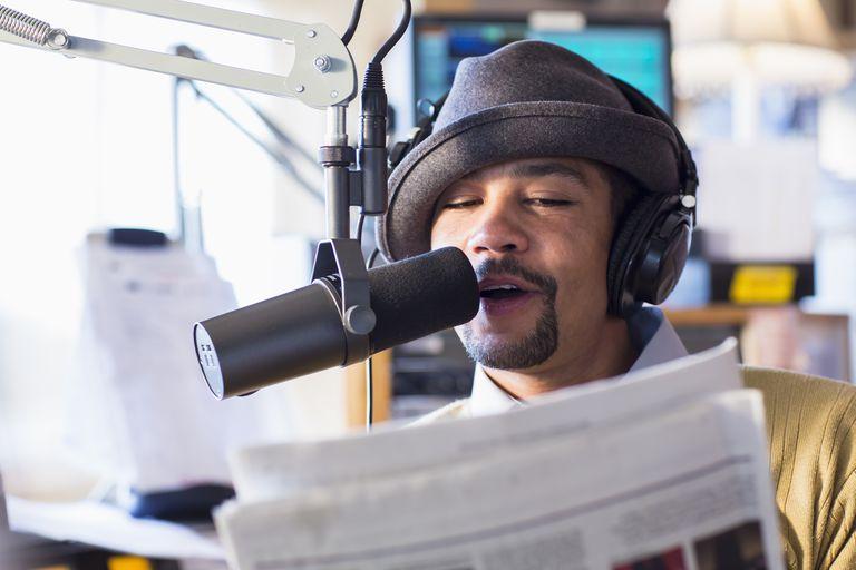 Mixed race disc jockey talking into mic in studio