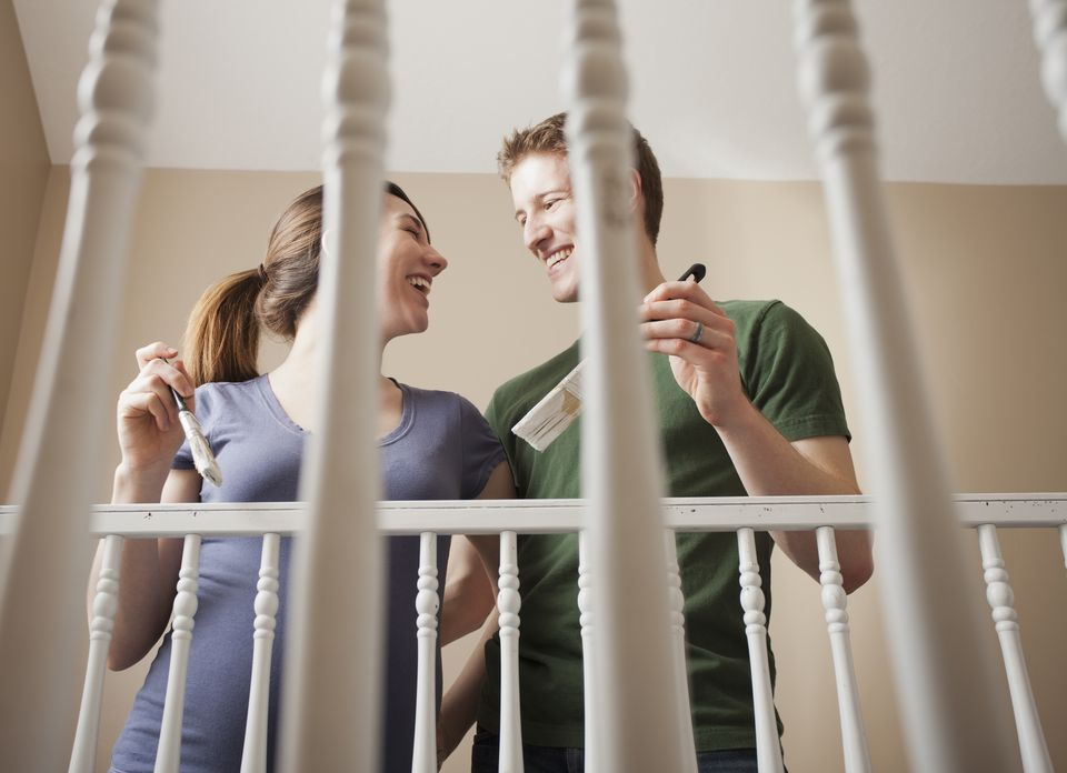 Low angle view of young couple standing face to face holding paint brush