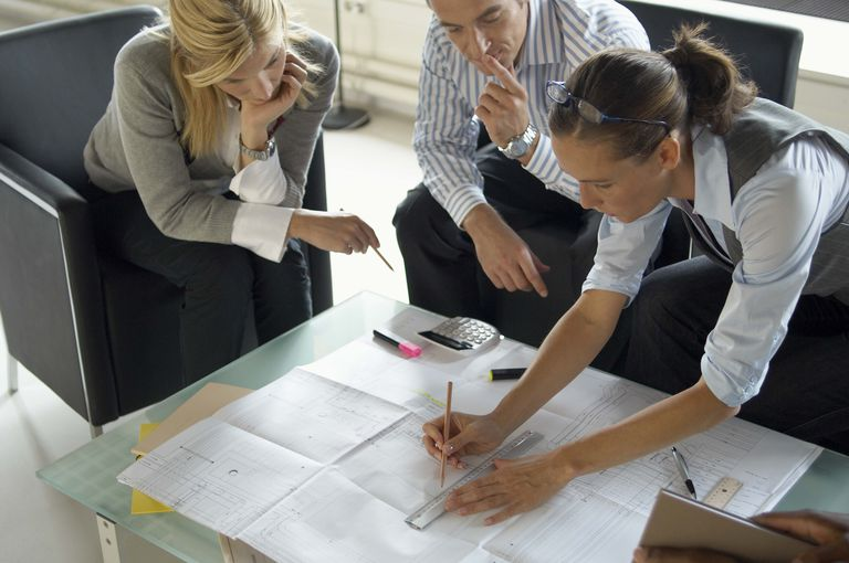 oung woman architect changing architectural drawings at business meeting with client couple