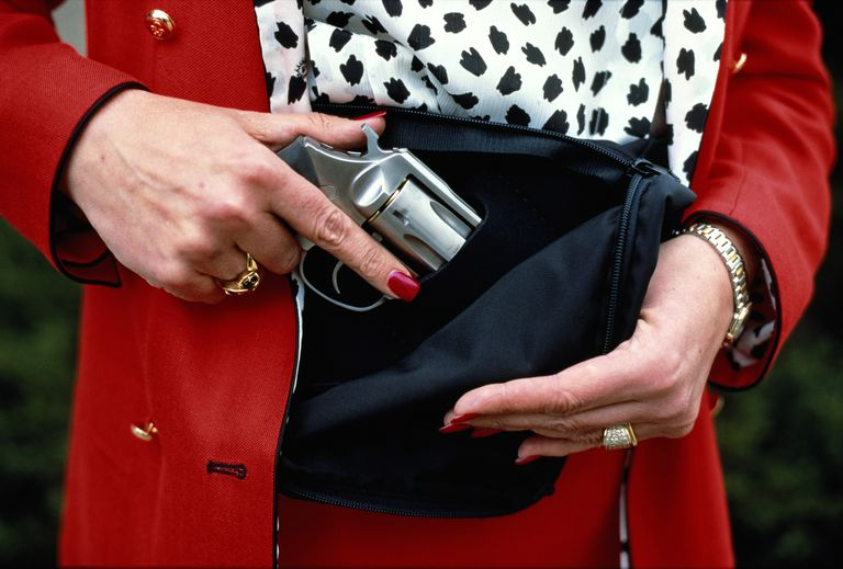 Woman concealing gun in handbag