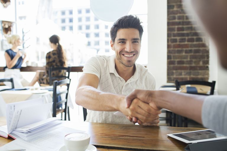 men shaking hands at table
